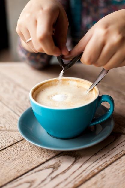 Nahaufnahme der weiblichen hand gießt zucker in kaffee über holzoberfläche Kostenlose Fotos