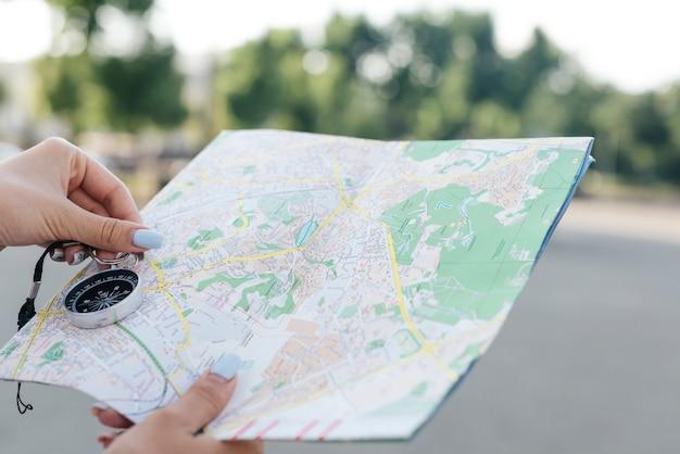 Nahaufnahme der weiblichen hand karte und navigationskompass halten Kostenlose Fotos