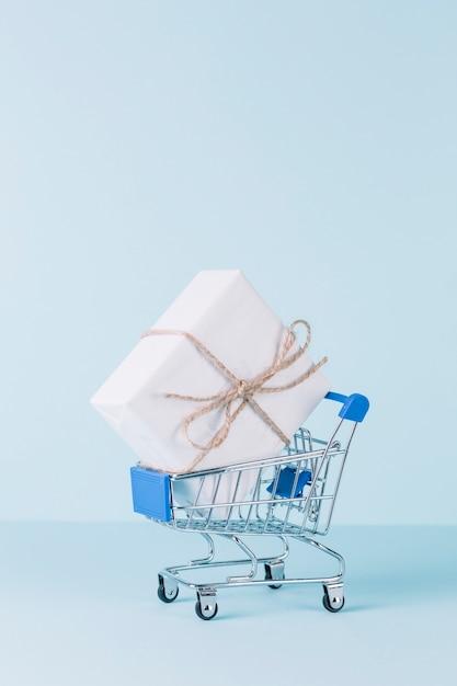 Nahaufnahme der weißen geschenkbox im einkaufswagen auf blauem hintergrund Kostenlose Fotos