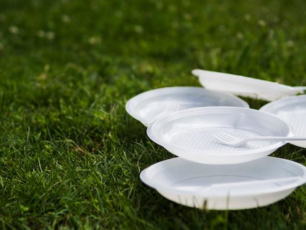 Nahaufnahme der weißen plastikplatte und der gabel auf gras am park Kostenlose Fotos