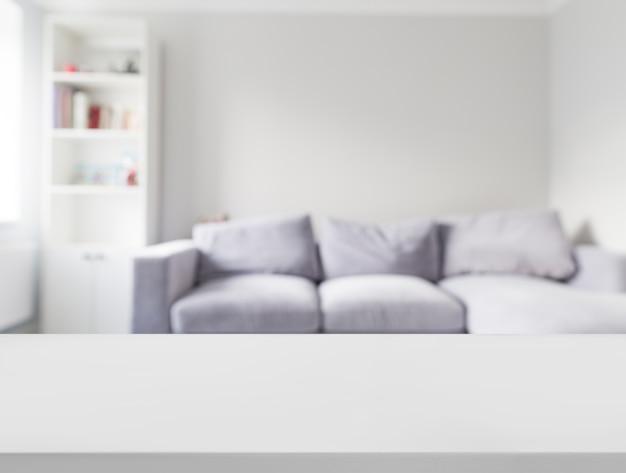 Nahaufnahme der weißen tabelle vor defocused sofa Kostenlose Fotos