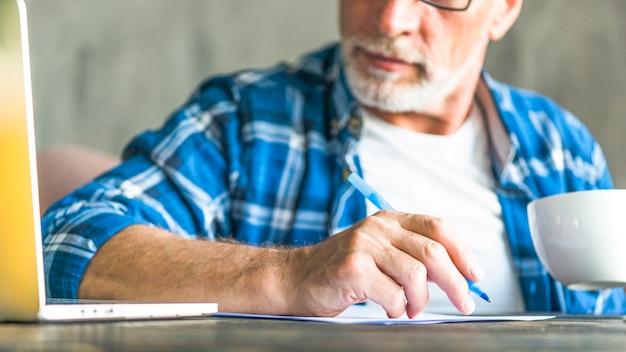 Nahaufnahme des älteren mannes den laptop betrachtend, der anmerkung macht Kostenlose Fotos