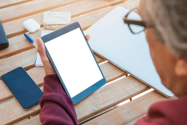 Nahaufnahme des älteren mannes digitale tablette mit leerem weißem schirm auf holztisch betrachtend Kostenlose Fotos