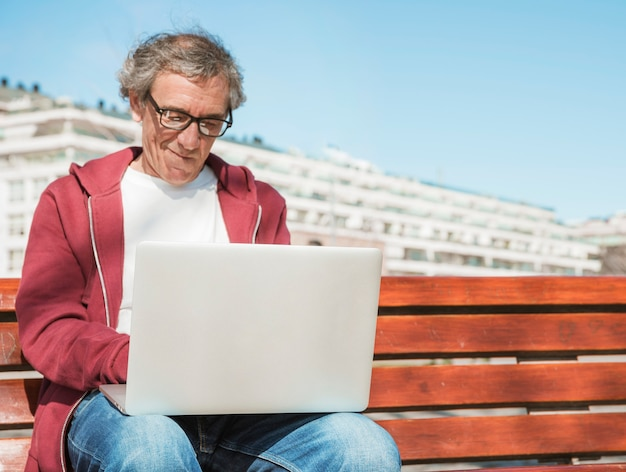 Nahaufnahme des älteren mannes sitzend auf bank unter verwendung des laptops Kostenlose Fotos