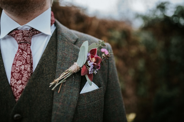 Nahaufnahme des anzugs eines bräutigams mit blumen und roter gemusterter krawatte mit bäumen auf dem hintergrund Kostenlose Fotos