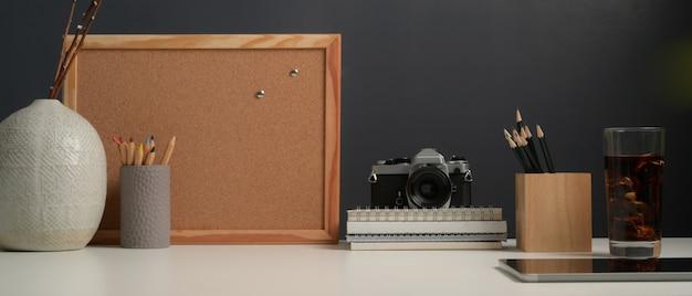 Nahaufnahme des arbeitstisches mit mock-up-anschlagtafel, briefpapier, kamera, zubehör und kopierraum im home-office-raum Premium Fotos