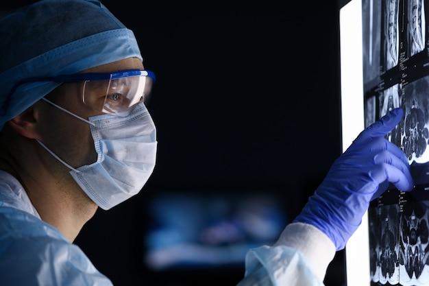 Nahaufnahme des arztes in der medizinischen uniform untersucht röntgen auf computerbildschirm. professionelles arbeiter-check-up-skiagramm des menschlichen körpers. modernes technologie- und medizinkonzept Premium Fotos