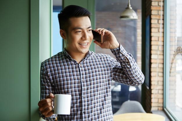 Nahaufnahme des asiatischen mannes einen becher kaffee halten, der im fenster bei der unterhaltung am telefon schaut Kostenlose Fotos