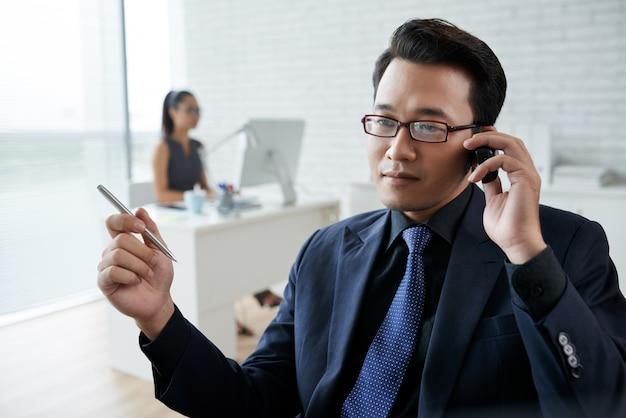 Nahaufnahme des asiatischen mannes sprechend am telefon im büro Kostenlose Fotos