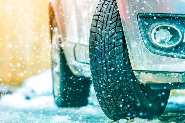 Nahaufnahme des autos drehen herein winterreifen auf schneebedeckter straße Premium Fotos