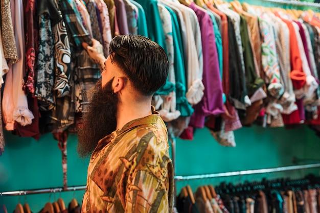 Nahaufnahme des bärtigen jungen mannes, der die hemden hängen an der schiene im shop betrachtet Kostenlose Fotos