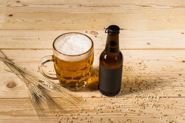 Nahaufnahme des bieres im glas und flasche mit den ohren des weizens auf hölzernem hintergrund Kostenlose Fotos