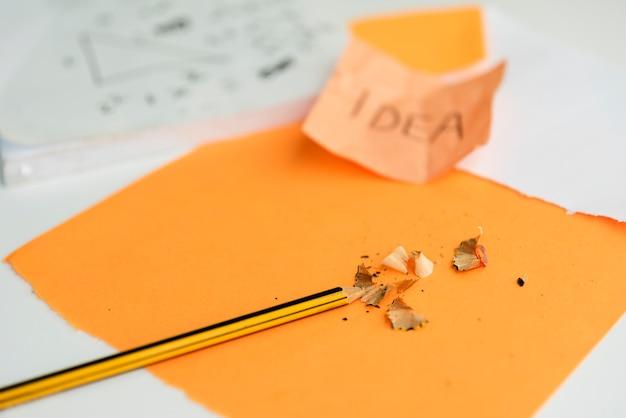 Nahaufnahme des bleistifts und des bleistifts, die auf orange papier rasieren Kostenlose Fotos