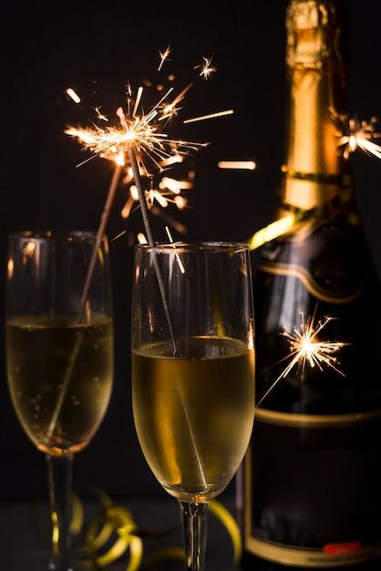 Nahaufnahme des champagners und der wunderkerze über schwarzem hintergrund Kostenlose Fotos