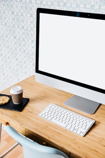 Nahaufnahme des computers und der tastatur auf hölzernem schreibtisch Kostenlose Fotos