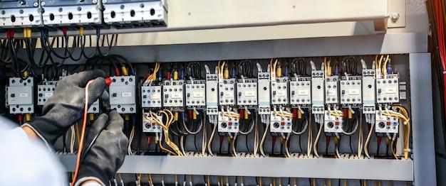 Nahaufnahme des elektrotechnikers unter verwendung von messgeräten zur überprüfung der elektrischen stromspannung am leistungsschalter. Premium Fotos