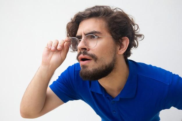 Nahaufnahme des fokussierten aufmerksamen kerls in den gläsern, die weg anstarren Kostenlose Fotos