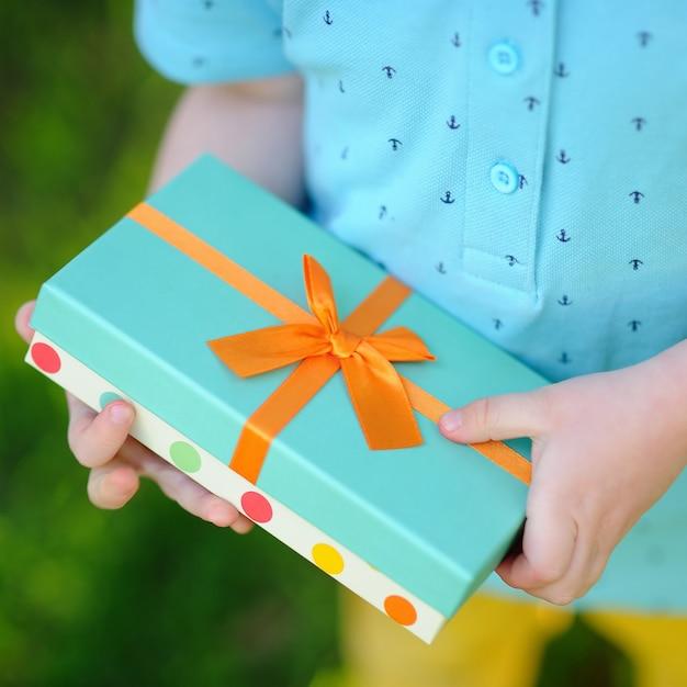 Nahaufnahme des freundlich eingewickelten geburtstagsgeschenks, das von einem kind gehalten wird Premium Fotos