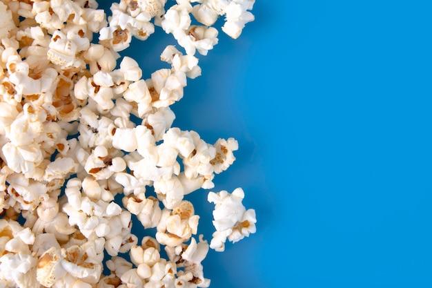 Nahaufnahme des frischen warmen popcorns auf blauem hintergrund. Premium Fotos