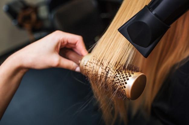Nahaufnahme des friseurs, der blondes haar mit fön und rundbürste von hand trocknet Premium Fotos
