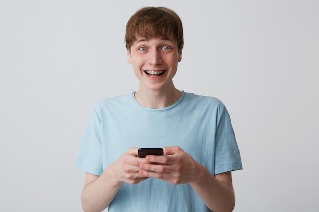 Nahaufnahme des fröhlichen aufgeregten jungen mannes mit zahnspangen auf zähnen trägt blaues t-shirt fühlt sich glücklich und verwendet smartphone lokalisiert über weiße wand Kostenlose Fotos