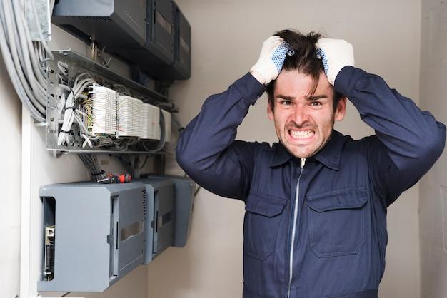 Nahaufnahme des frustrierten männlichen elektrikers, der nahe elektrischem brett steht Kostenlose Fotos