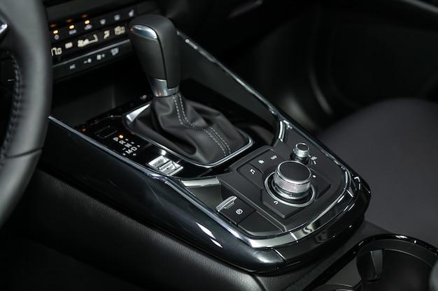 Nahaufnahme des gaspedalgriffs und der knöpfe mit moderner mittelkonsole mit kontrollen. automatikgetriebe des autos, autoinnenraum Premium Fotos