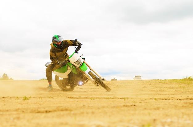 Nahaufnahme des gebirgsmotocrossrennens im sandweg in der tageszeit. Premium Fotos