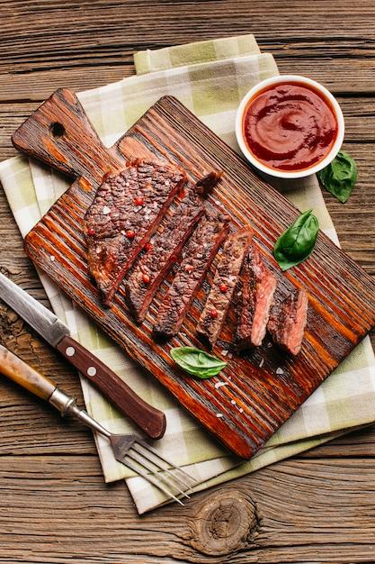 Nahaufnahme des gebratenen steaks mit soße auf holztisch Kostenlose Fotos
