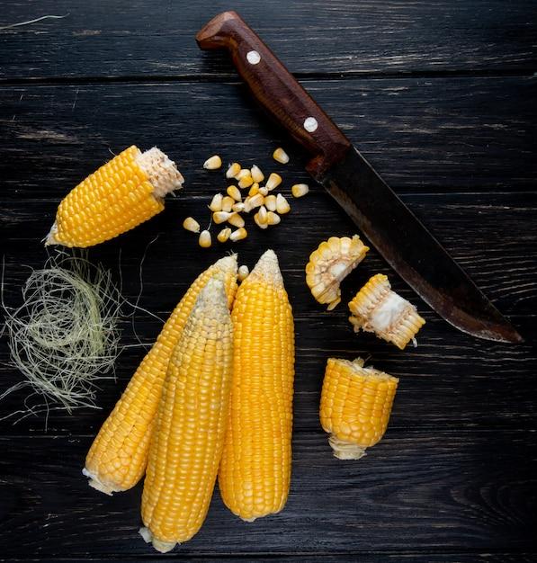 Nahaufnahme des gekochten ganzen und geschnittenen maissamens der körner mit seide und messer auf schwarzer oberfläche Kostenlose Fotos