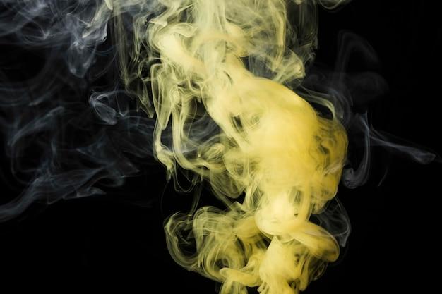 Nahaufnahme des gelben rauches gegen schwarzen hintergrund Kostenlose Fotos