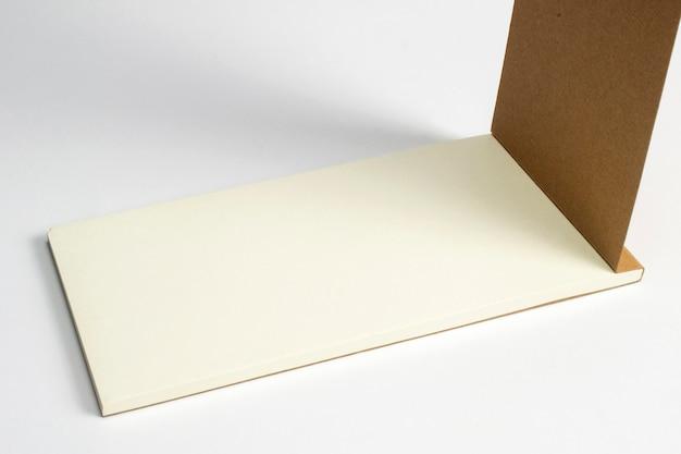 Nahaufnahme des geöffneten tagebuchs mit papp-hardcover und leeren seiten lokalisiert auf weiß. Kostenlose Fotos