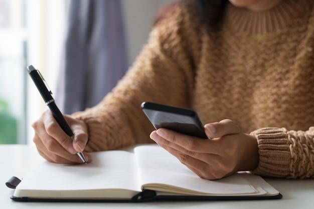 Nahaufnahme des geschäftsfrauplanungszeitplans unter verwendung des smartphone Kostenlose Fotos