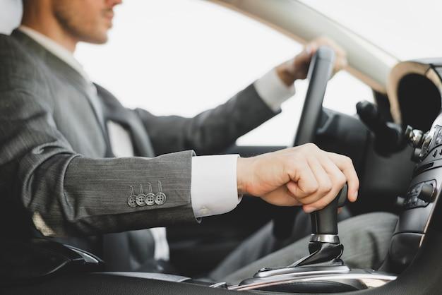 Nahaufnahme des geschäftsmannes das auto antreibend Kostenlose Fotos