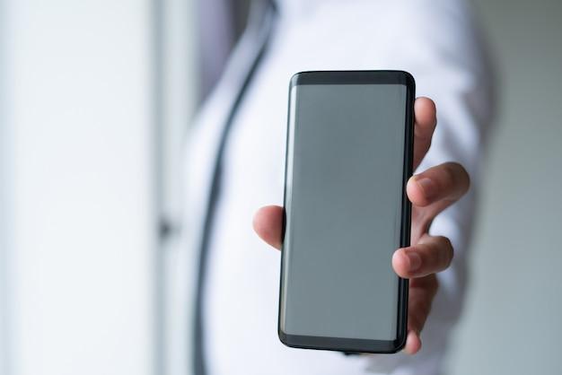 Nahaufnahme des geschäftsmannes leeren smartphoneschirm zeigend Kostenlose Fotos