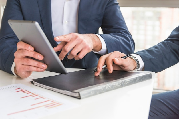Nahaufnahme des Geschäftsmannes Finanzbericht auf digitaler Tablette besprechend Kostenlose Fotos