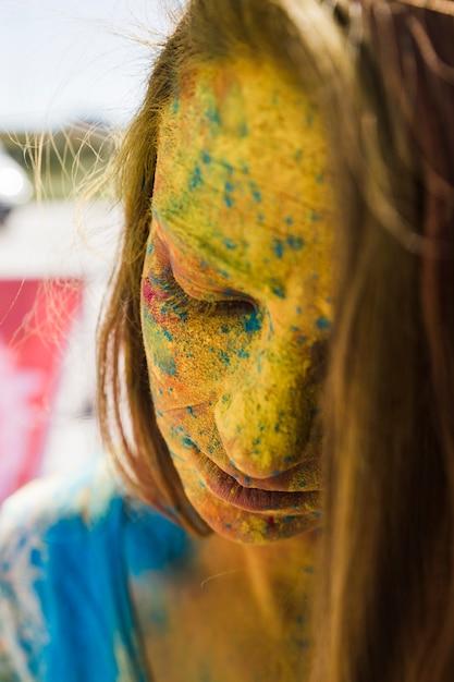 Nahaufnahme des gesichtes der frau bedeckt mit gelber holi farbe Kostenlose Fotos