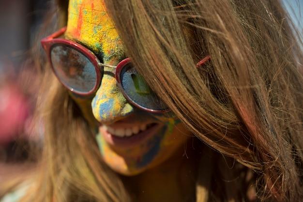 Nahaufnahme des gesichtes der frau bedeckt mit holi farbtragenden brillen Kostenlose Fotos