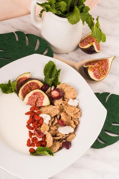 Nahaufnahme des gesunden frühstücks auf platte nahe gefälschten blättern und krug tadellosen blättern Kostenlose Fotos