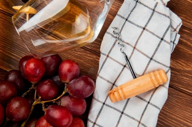 Nahaufnahme des glases weißwein und der traube mit korkenzieher auf stoff auf holztisch Kostenlose Fotos