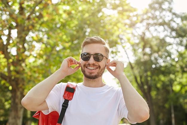 Nahaufnahme des glücklichen hipsters, der an sonnigem tag durch park geht, sonnenbrille und weißes t-shirt trägt, kopfhörer in ohren einführt, in guter stimmung ist Kostenlose Fotos