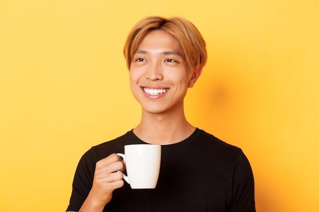 Nahaufnahme des glücklichen hübschen jungen asiatischen kerls mit blondem haar, träumerisch aussehend und lächelnd, während kaffee oder tee trinkend, über gelber wand stehend. Kostenlose Fotos