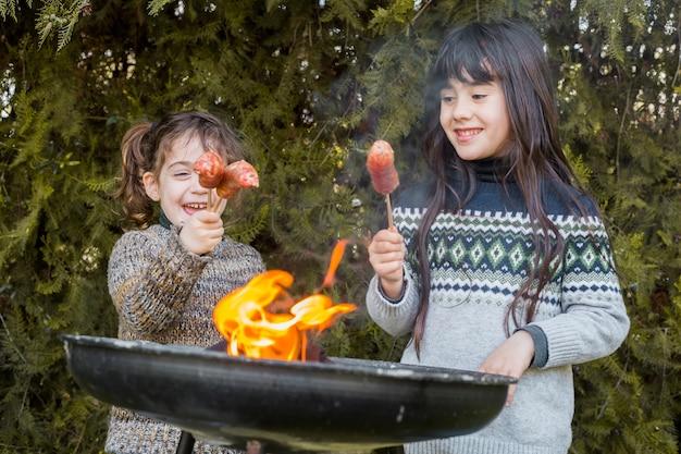 Nahaufnahme des grills vor zwei glücklichen mädchen, die würste halten Kostenlose Fotos