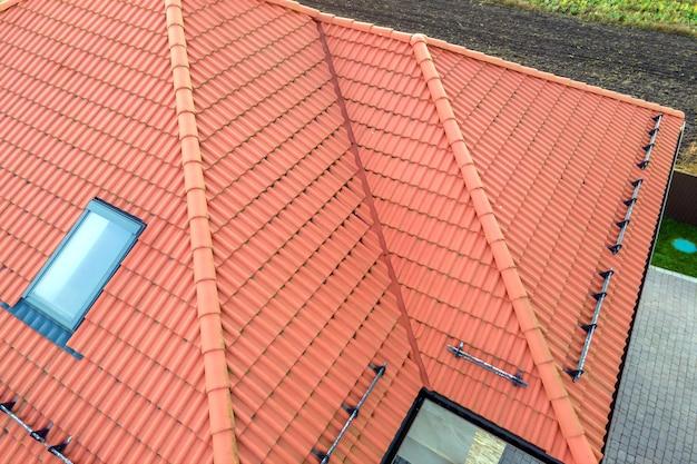 Nahaufnahme des hausziegeldaches mit gelber schindelabdeckung und dachglasfenstern. Premium Fotos