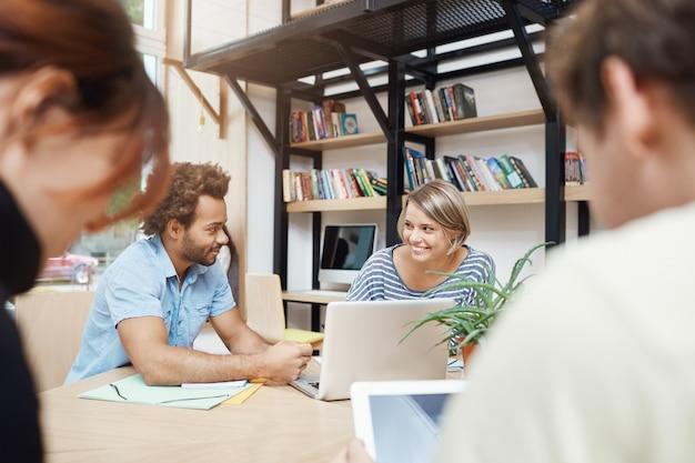 Nahaufnahme des jungen designerteams, das im coworking space am tisch sitzt, über gewinne von alten projekten spricht, statistiken auf laptop durchschaut, gespräch führt Kostenlose Fotos