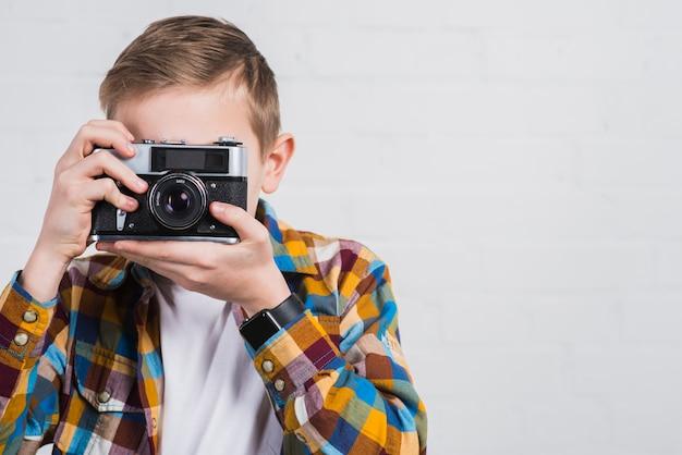 Nahaufnahme des jungen foto mit weinlesekamera gegen weißen hintergrund machend Kostenlose Fotos