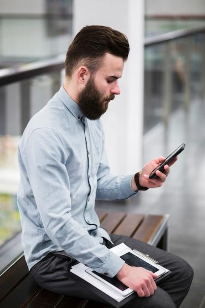 Nahaufnahme des jungen geschäftsmannes sitzend auf bank unter verwendung des handys Kostenlose Fotos