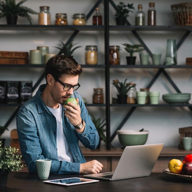 Nahaufnahme des jungen mannes den grünen apfel essend, der digitale tablette betrachtet Kostenlose Fotos