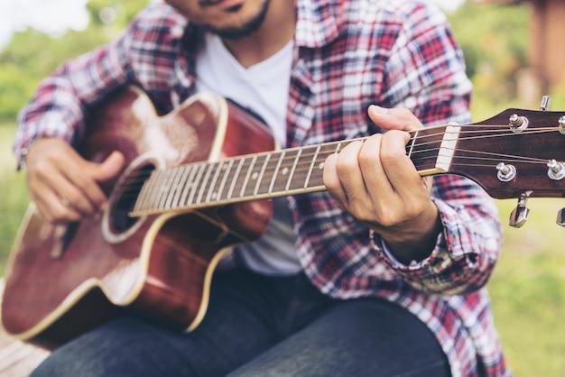 Nahaufnahme des jungen mannes gitarre spielen. Premium Fotos