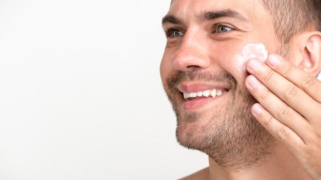 Nahaufnahme des jungen mannes lächelnd, creme auf gesicht auftragend Kostenlose Fotos